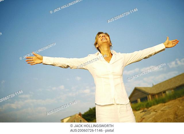 Mature woman smiling with her arms outstretched