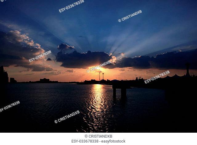 Blue sky and sun rays. Sunset over Abu Dhabi, United Arab Emirates
