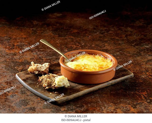 Emmental, Gruyere and Calvados cheese baked in terracotta dish and torn rustic wholemeal bread