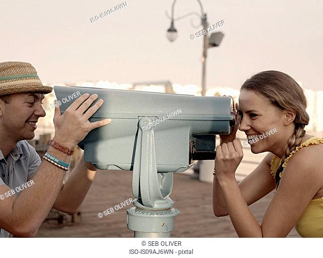 Young couple looking at each other through coin binoculars on Santa Monica pier, California, USA