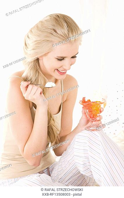 Woman eating jelly with cream
