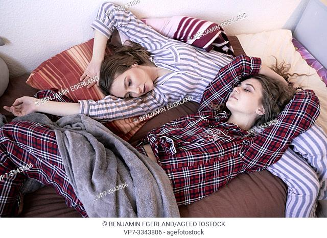 two young women laying in bed together, wearing pyjamas