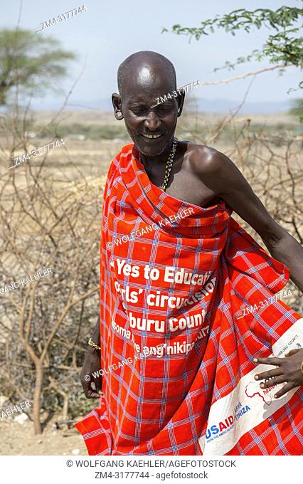 A man is wearing a cloth from US Aid with Yes to education and No to girl circumcision in a Samburu village near Samburu National Reserve in Kenya