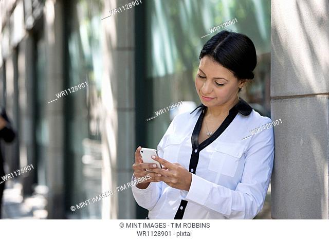 Business people outdoors, keeping in touch while on the go. A woman in a white jacket checking her phone