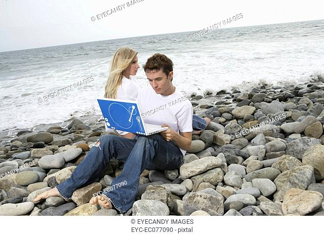Portrait of young couple sitting on rocky beach with laptop