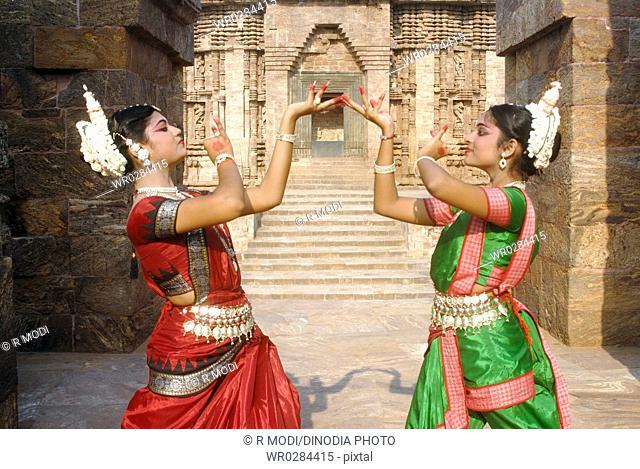 Dancers performing classical traditional odissi dance in front of Sun Temple , Konarak , Orissa , India MR 736C,736D