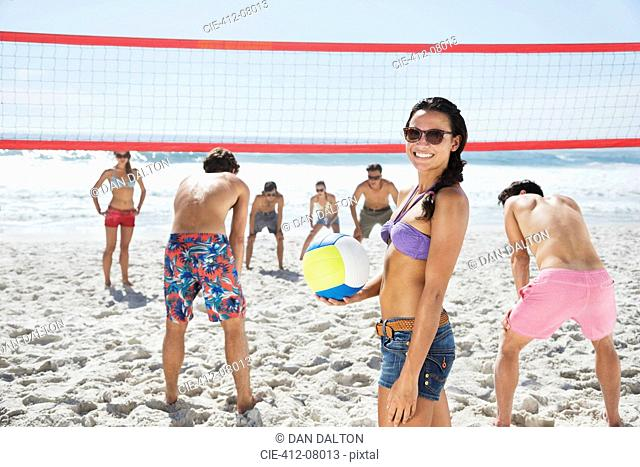 Portrait of smiling woman playing beach volleyball with friends