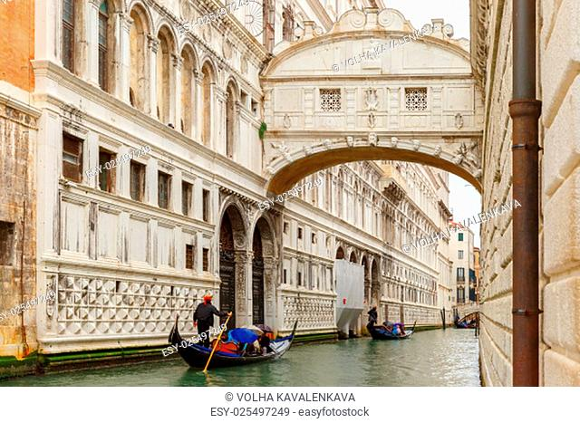 Traditional gondolas ride under the Bridge of Sighs on lateral narrow canal in rainy weather in Venice, Italy