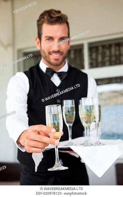 Handsome waiter offering flute of champagne