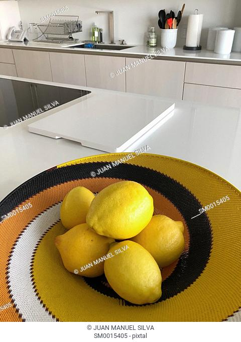 Basket with lemons in modern kitchen