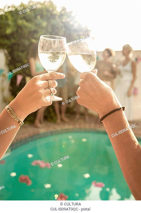 Arms of two people holding wine glasses making toast in front of swimming pool