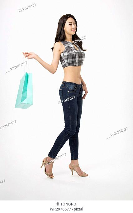 Side view of young smiling woman walking holding a shopping bag
