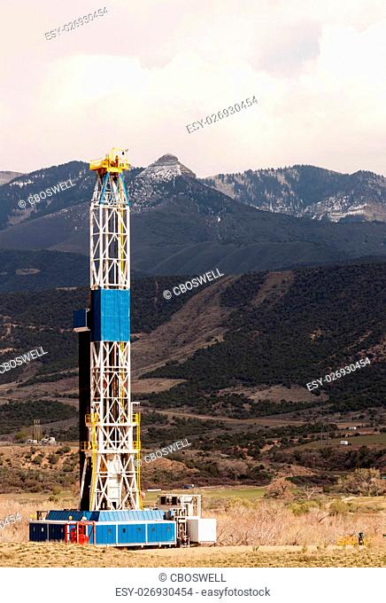An oil derrick stands late in the day against the mountains