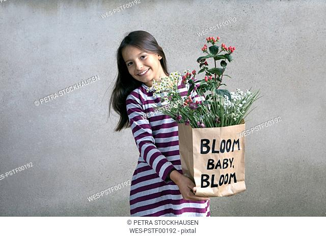 Portrait of happy girl holding paper bag with flowers
