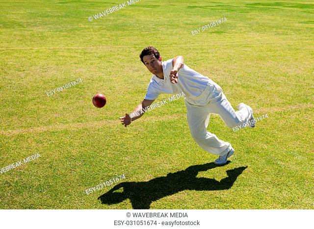 Full length of player catching ball on field