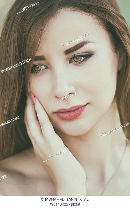 Beautiful young woman hand touching face outdoors