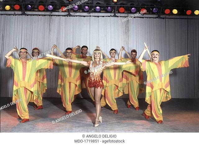 Raffaella Carrà with her dancers. Italian showgirl and TV presenter Raffaella Carrà (Raffaella Pelloni) wearing a stage costume and dancing with her dancers in...