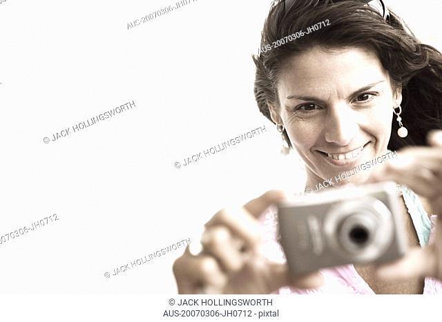 Close-up of a mid adult woman taking a picture with a digital camera