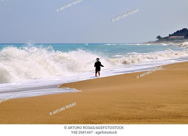 A boy front the waves in L'Arenal Beach of L'Hospitalet de L'Infant, Tarragona. Catalonia, Spain