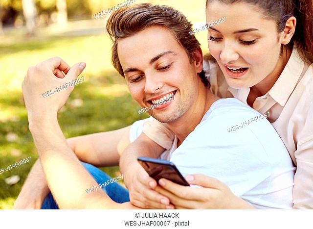 Young couple looking at smartphone at a park