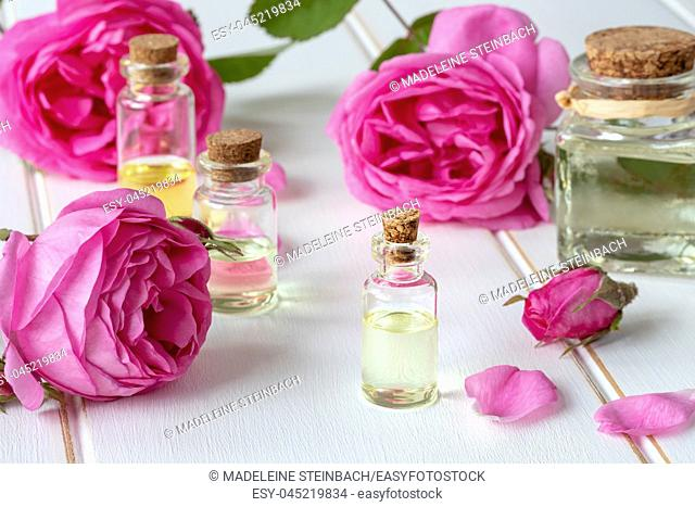 A bottle of essential oil with fresh roses