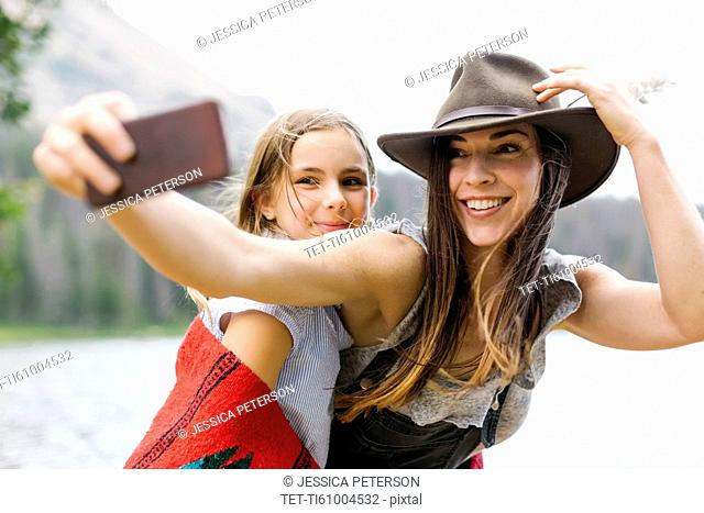 Mother and daughter (8-9) taking selfie