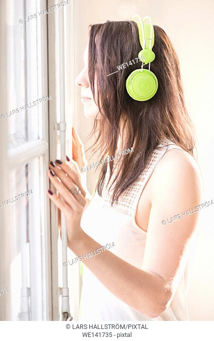 Woman standing by a window, looking away. She is listening to music in green headphones. Lifestyle image of carefree relaxation