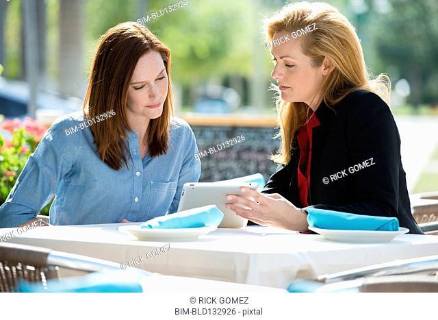 Caucasian businesswomen using digital tablet at lunch