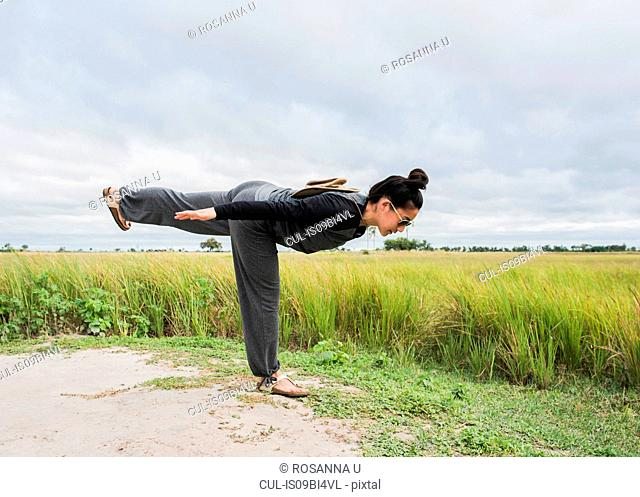 Young female tourist practicing yoga, Okavango Delta, Botswana, Africa