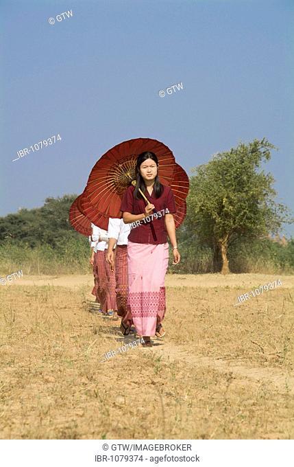 Young Burmese women with a parasol crossing a field, Bagan, Myanmar