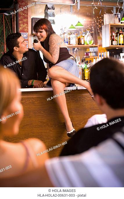 Young woman singing to bartender