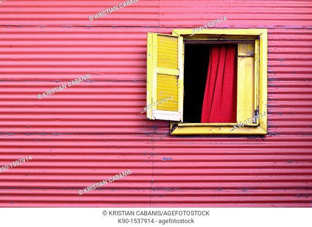 Window to the world: Red house of tin plates with one open, yellow window in El Caminito, La Boca, Buenos Aires, Argentina, South America