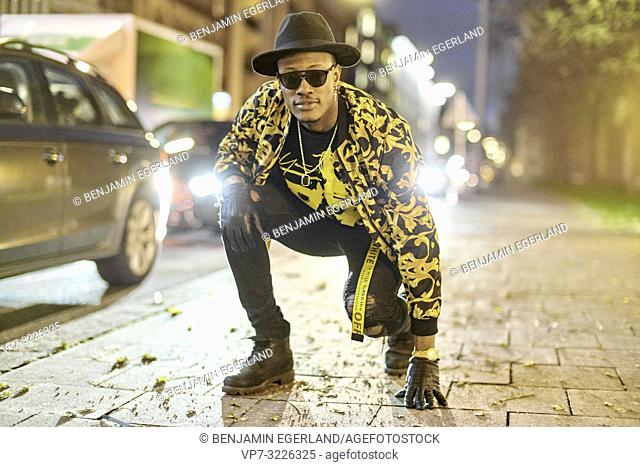 fancy blogger man crouching at city street at night, wearing stylish outfit, car lights, traffic, cool attitude, at Türkenstraße in Munich, Germany