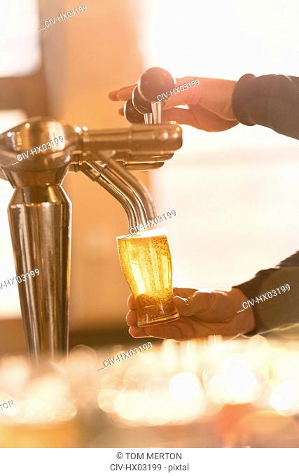 Bartender filling pint glass with beer at beer tap in bar