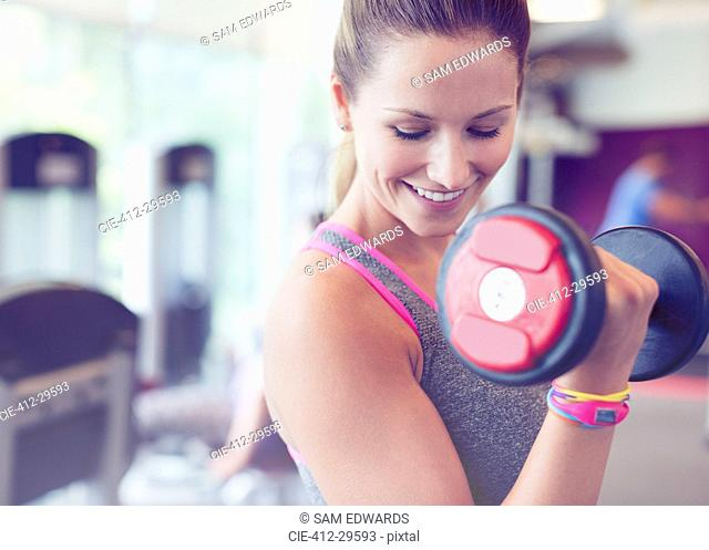 Close up smiling woman doing dumbbell biceps curls at gym