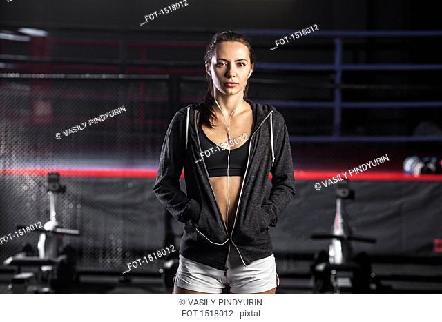 Female athlete with hands in pockets standing at gym