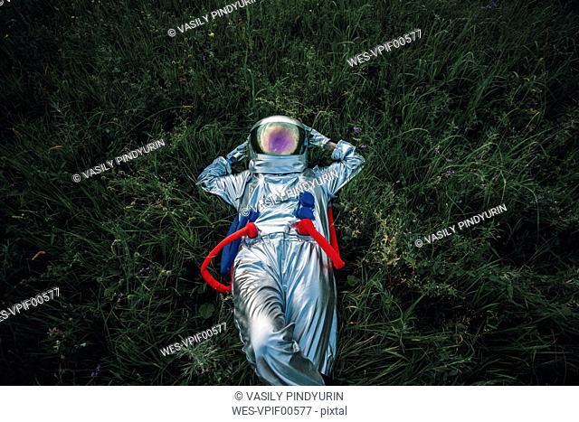 Spaceman exploring nature, relaxing in meadow