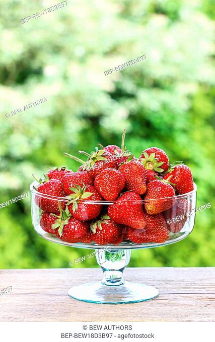 Fresh ripe strawberries in glass bowl