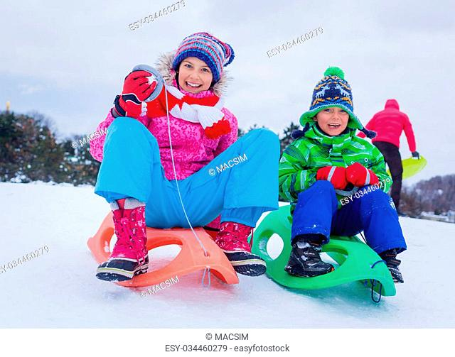 Happy cute girl with her brother sledding in the snow mountain