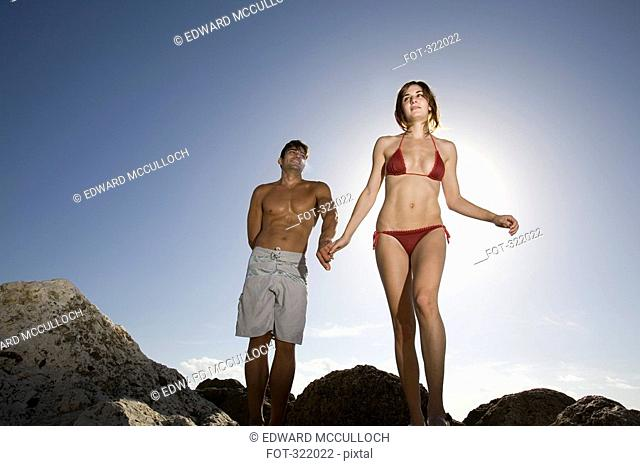 Couple walking across rocks and holding hands