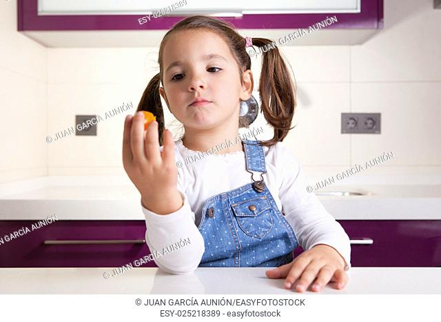 Little girl observing a colorful cherry tomatoe before tasting it