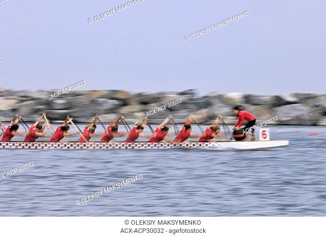Women paddlers team in a Dragon boat racing competition. Toronto, Ontario, Canada