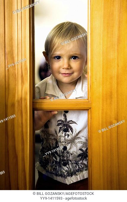 Young boy looking through window - Fort Lauderdale, Florida USA