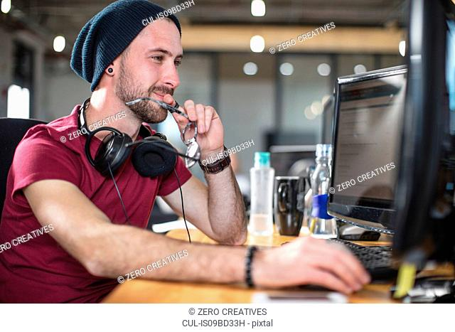 Young man working at his computer in office