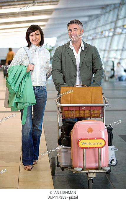 Mature Couple With Luggage In Airport Departure Lounge