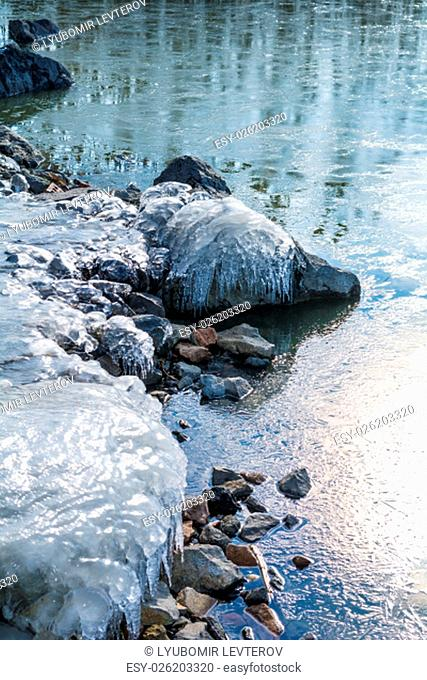 Frozen rocks with ice in the winter pond