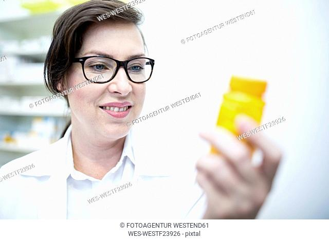 Smiling pharmacist holding pill box in pharmacy