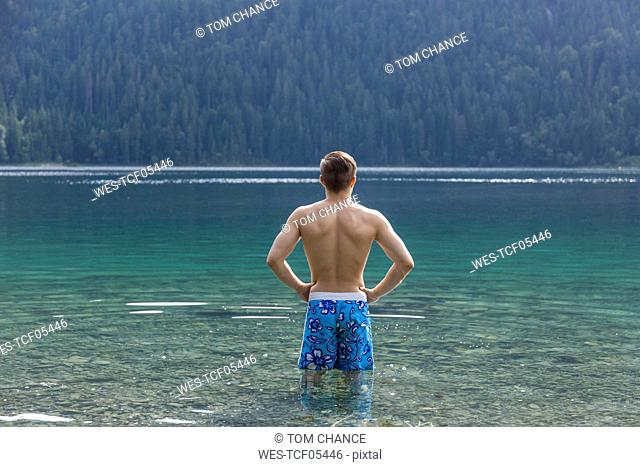 Germany, Bavaria, Eibsee, back view of young man standing in water