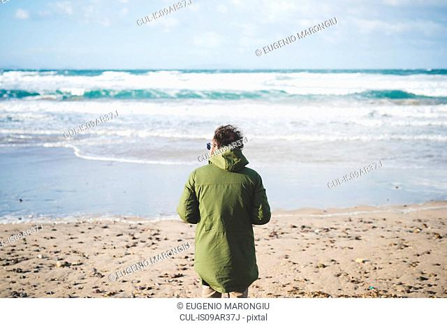 Rear view of man looking out to sea from windy beach, Sorso, Sassari, Sardinia, Italy