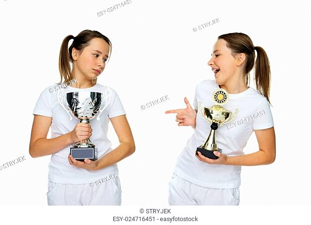 Two Young Pretty Girls in White Holding Trophies Pose. Isolated on Pure White Background